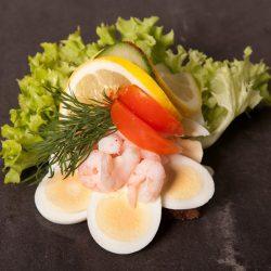 Et billede af et stykke smørrebrød med æg, rejer, tomatskiver, agurkskiver og noget salat