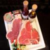 På billedet vises 2 t-bone steak. De ligger på en tallerken hvor der i siden står 2 olier.