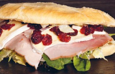 Billedet viser en lækker sandwich med hamburgerryg, ost og salat